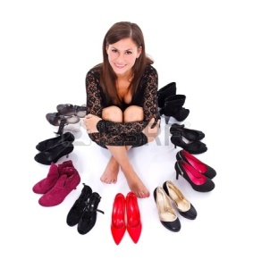 16639323-smiling-young-woman-sitting-among-her-shoes